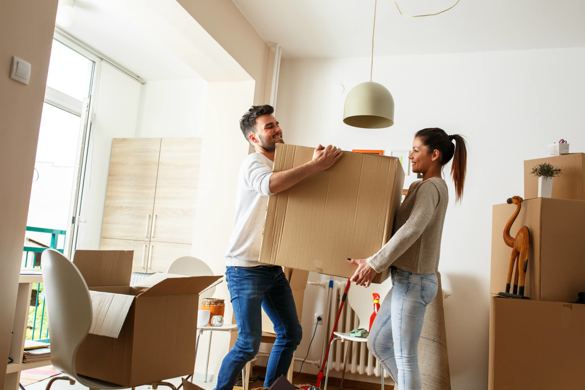 Young couple packing and moving boxes after selling their home